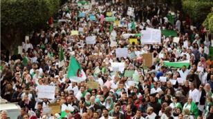 Trabajadores del sector de la salud con banderas de Argelia y pancanrtas durante una protesta en Argel  para pedir la partida del presidente Abdelaziz Buteflika el 19 de marzo de 2019