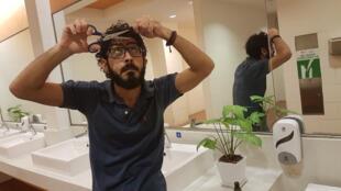 السوري حسن القنطار يحاول قص شعره في حمامات مطار كوالالمبور حيث أقام 7 أشهر