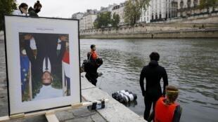 Des membres d'Action Climat Paris, qui avient décroché des portraits d'Emmenul Macron, dans les mairies s'apprêtent à les poser sur la Seine à Paris le 15 octobre 2020