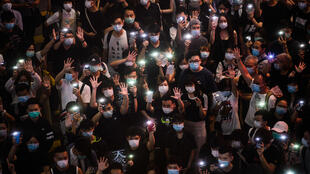 Hong Kongers hold up their mobile phones during a rally in Causeway Bay on June 12 to mark the one-year anniversary of the start of major pro-democracy protests in the city