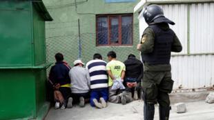 Un oficial de policía junto a personas detenidas durante los enfrentamientos entre partidarios del presidente boliviano Evo Morales y simpatizantes de la oposición en La Paz, Bolivia el 11 de noviembre de 2019.