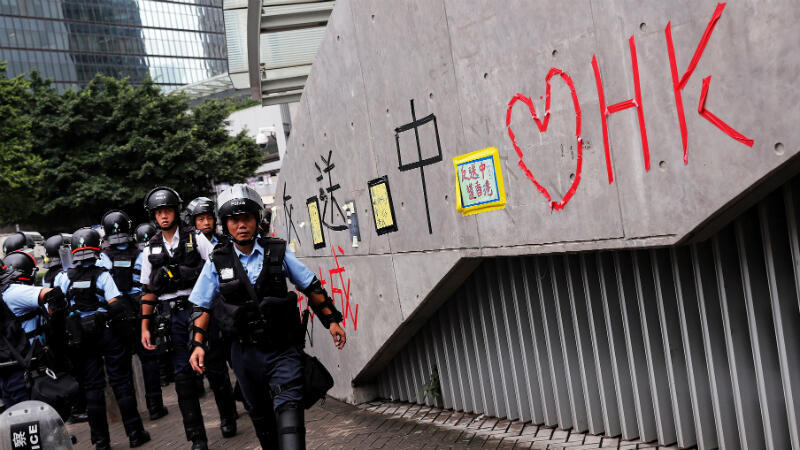 Tyrone Siu, REUTERS | Riot police officers pass a wall covered with messages written by pro-democracy supporters