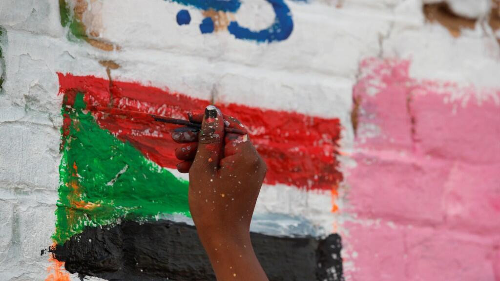 Amna Almahi works on a mural near the defence ministry compound in Khartoum, Sudan, April 22, 2019. Picture taken April 22, 2019.