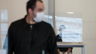 A man sits behind a protective plastic panel, during a distribution of protective face masks organised by the city of Mulhouse, eastern France, on May 16, 2020, as France eases lockdown measures taken to curb the spread of the COVID-19 pandemic, caused by the novel coronavirus.