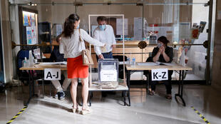 A voter hands in a ballot at a polling place in Paris on June 28, 2020.