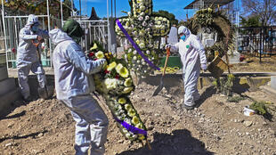 Gravediggers lay a wreath for a victim of Covid-19 at a cemetery in Ecatepec near Mexico City
