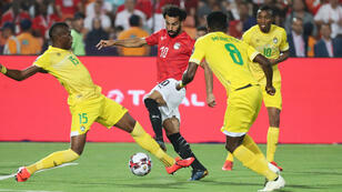 Mohamed Salah disputa un balón frente a los zimbabwenses Teenage Hadebe (izquierda) y Marshall Munetsi en el partido inaugural de la Copa Africana de Naciones el 21 de junio de 2019 en El Cairo, Egipto.