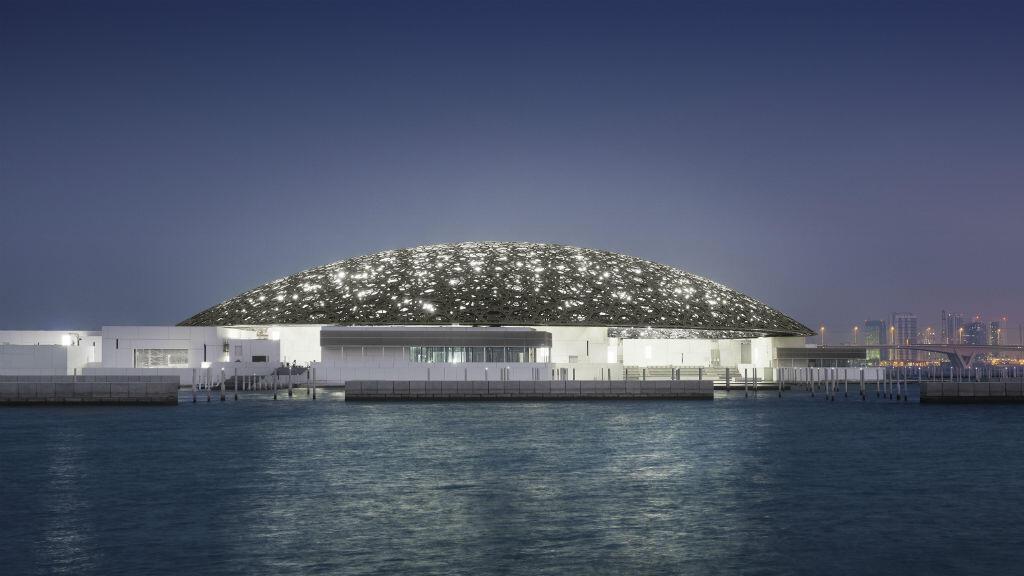Extérieur du Louvre Abu Dhabi avec la ville à l'horizon.