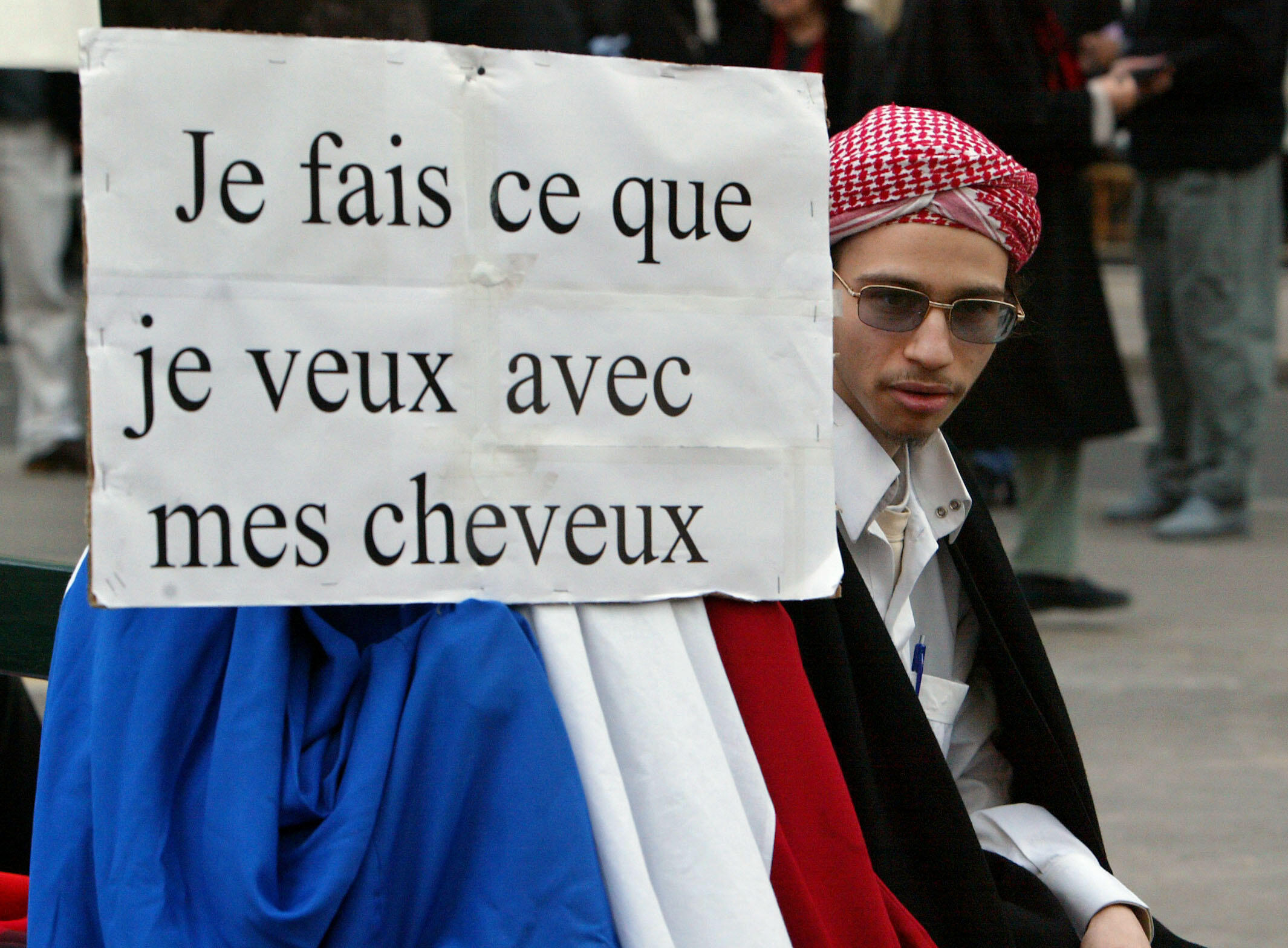 """Farid Benyettou pictured in 2004 next to a sign reading """"I do what I like with my hair"""", during a protest against a law banning hijabs and other religious signs from French schools."""