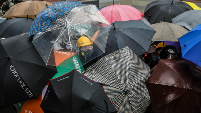 Dale De La Ray, AFP | Protesters use umbrellas to shield themselves against the pepper spray used by police