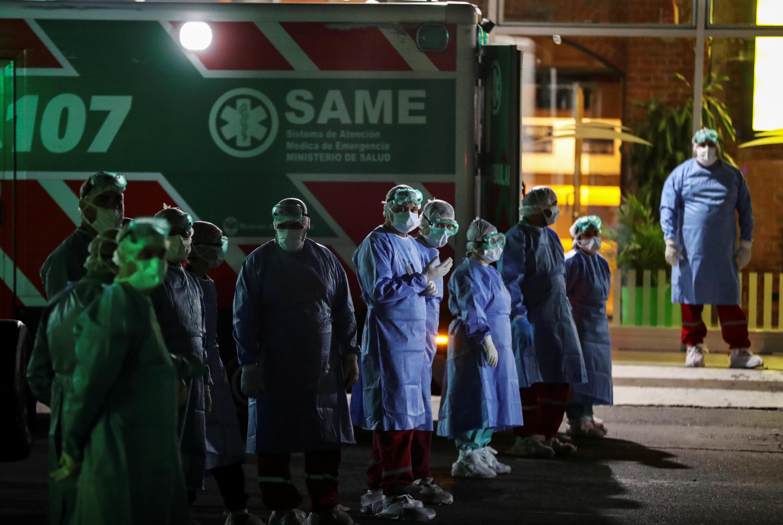 Los trabajadores de la salud se paran junto a las ambulancias estacionadas en los muelles de Buenos Aires después de que se sospecha que un pasajero ha sido infectado con el virus de la Coruña, Argentina, el 20 de marzo de 2020.