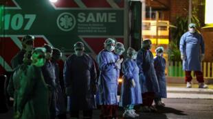 عاملون بقطاع الصحة يقفون بجانب سيارات الإسعاف المتوقفة عند أرصفة بوينس آيرس بعد الاشتباه في إصابة أحد الركاب بفيروس كورونا، الأرجنتين، 20 مارس/آذار 2020.