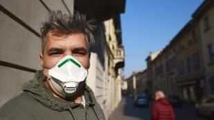 A resident wearing a protective respiratory mask looks on in a street of Codogno, southeast of Milan, on February 22, 2020.