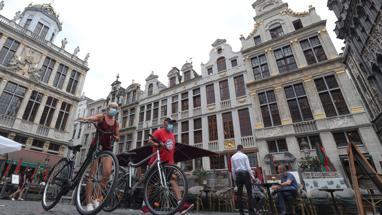 Personas con mascarillas protectoras empujan sus bicicletas en la Grand-Place de Bruselas, en Bélgica, 20 de agosto de 2020.