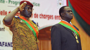 Burkina Faso's PM Lieutenant Colonel Isaac Zida (L) salutes as he stands next to interim civilian President Michel Kafando on November 21 2014, at a stadium in Ouagadougou.