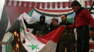 Des combattants de la coalition islamiste, qui a conquis Idleb, brûlent le drapeau syrien, le 29 mars 2015.