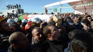 Des pompiers algériens portent le cercueil d'Hocine Aït Ahmed, vendredi 1er janvier 2016, dans son village natal de Kabylie qui porte le même nom que lui.