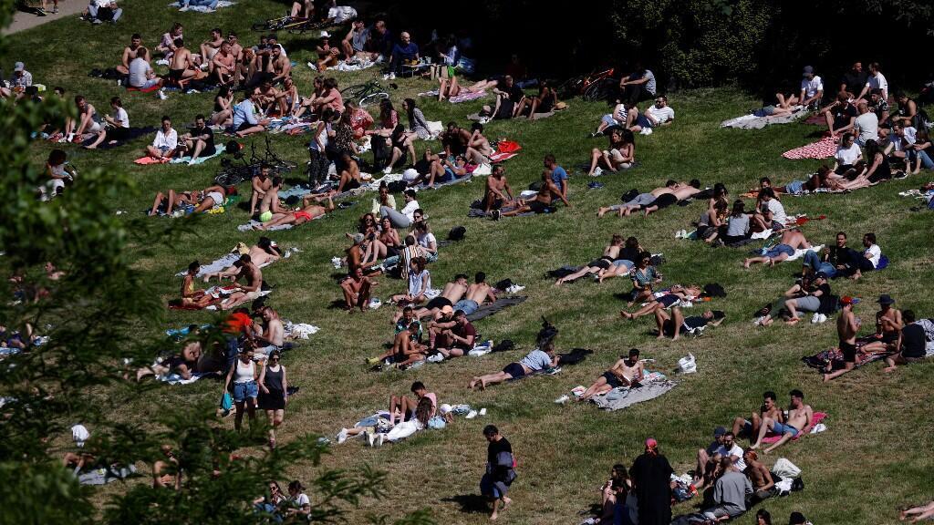 Gente disfruta del clima soleado en el Buttes Chaumont cuando los parques de París se vuelven a abrir en medio del brote deL Covid-19, en París, Francia, el 31 de mayo de 2020.