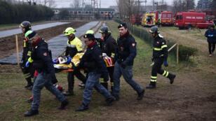 Des sauveteurs et des policiers transportent une victime sur une civière sur le lieu d'un déraillement, le 25 janvier 2018 près de Milan.