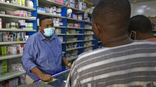 صيدلي يرتدي قناعًا وقائيًا يقدم خدمات للعملاء في صيدلية بالعاصمة السودانية الخرطوم في 18 حزيران/يونيو 2020