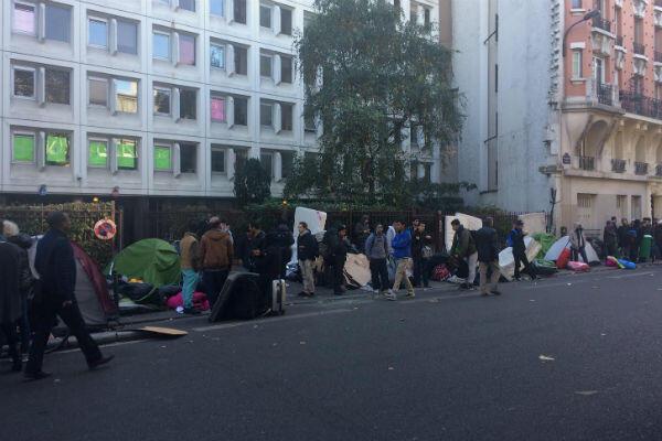 Les migrants attendant la fin des opérations de police. Ils patientent à 10 mètres des forces de l'ordre avant de se réapproprier les trottoirs parisiens.