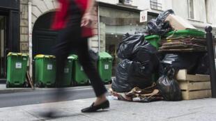 Une femme passe devant des poubelles qui s'entassent, mercredi 8 juin 2016, à Paris.