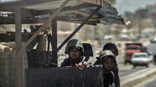 Des policiers égyptiens tenant un checkpoint sur une route menant vers le le Nord-Sinaï en juillet 2018.