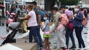 La gente usa máscaras faciales cerca de la frontera entre Venezuela y Colombia después de que el gobierno colombiano decidiera cerrar el puente internacional Simón Bolívar como medida preventiva en respuesta a la propagación de la enfermedad coronavirus (COVID-19) en San Antonio, Táchira, Venezuela el 14 de marzo de 2020.