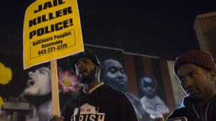 À Baltimore, un jeune homme manifeste, dans le nuit du 16 au 17 décembre, pour demander que le policier soit inculpé.