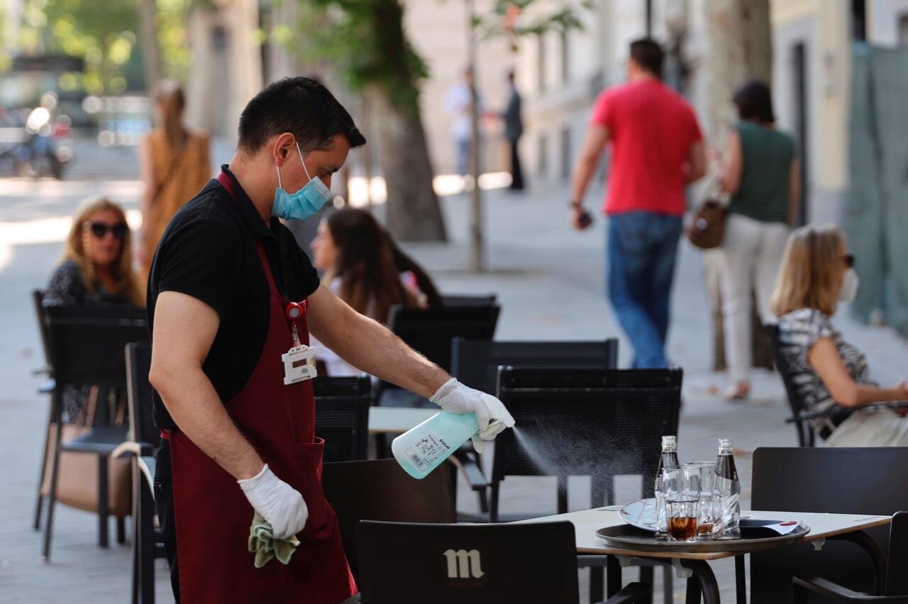 Archivo-Un camarero desinfecta una mesa en una terraza del centro de Madrid, España, el 29 de julio de 2020.