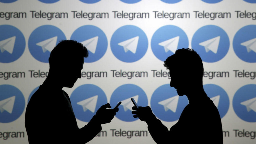 Dos hombres posan con teléfonos inteligentes frente a una pantalla que muestra los logotipos de Telegram, el 18 de noviembre de 2015