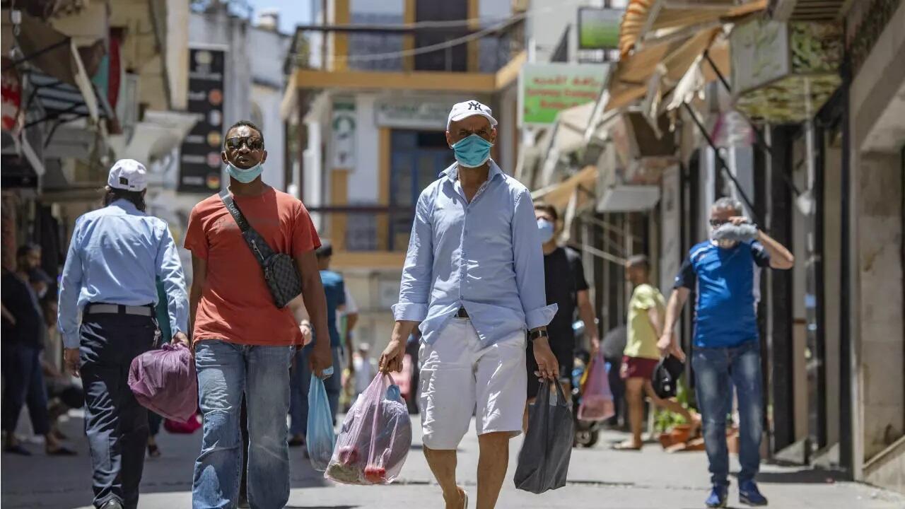 أشخاص يرتدون أقنعة في أحد شوارع البلدة القديمة بطنجة، بعد إعلان تدابير الاحتواء. 14 يوليو/تموز 2020.