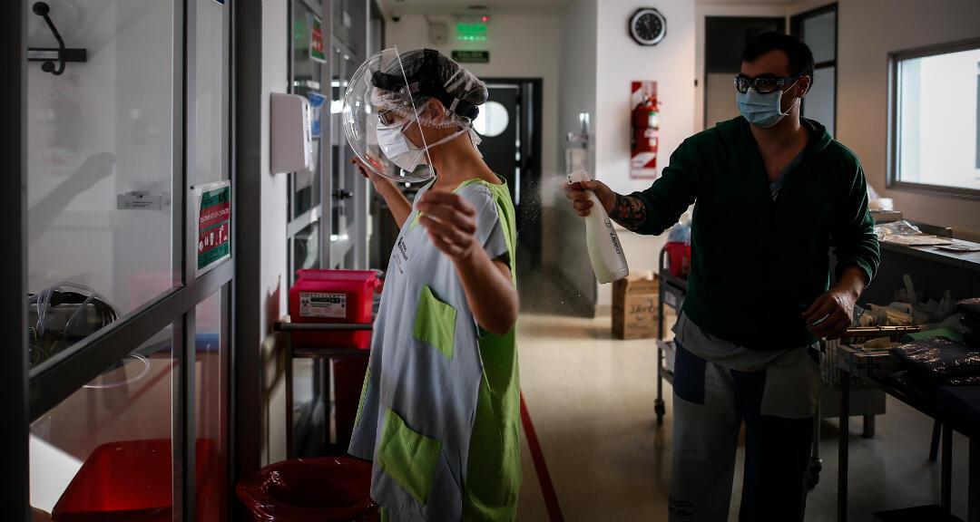 Médicos se desinfectan entre sí luego de realizar un control a pacientes de cuidado intensivo en el Hospital El Cruce de Florencia Varela el 30 de julio de 2020, en Buenos Aires, Argentina.