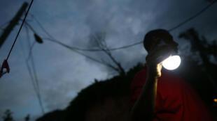Un puertorriqueño usa una lámpara solar mientras reparan el sistema eléctrico de la isla. 11 de mayo de 2018.