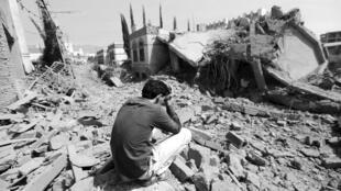 Foto de archivo de un guardia que se sienta en los escombros de la casa de brigada Fouad al-Emad, un comandante del ejército leal a los Huzis, después de los ataques aéreos que destruyeron a Saná, Yemen, el 15 de junio de 2015.