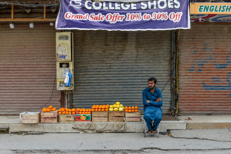 Un homme vend des oranges devant des magasins fermés sur un marché durant la pandémie de Covid-19 au Pakistan, à Rawalpindi, le 11 avril 2020.