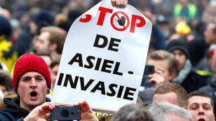 """""""Detengan la invasión de asilo"""", dice un cartel durante una manifestación flamenca en Bruselas, Bélgica, en oposición al Pacto por la Migración de Marrakesh el 16 de diciembre de 2018."""