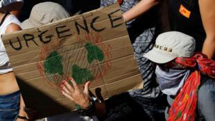 """Cartel en donde se lee la palabra """"Urgencia"""", durante una manifestación contra el G7 en Hendaya, Francia. 24 de agosto de 2019."""