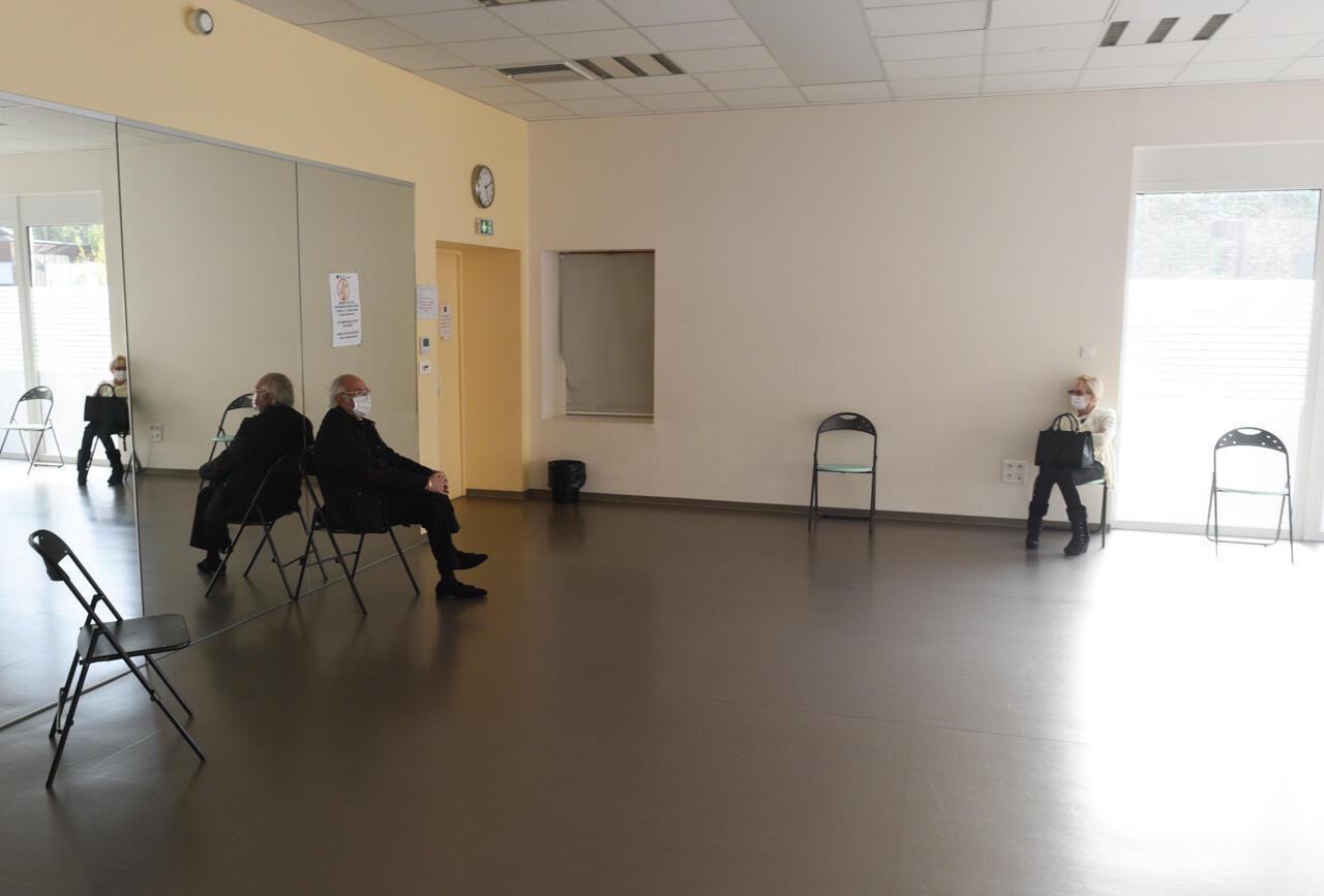 La grande salle d'attente du centre Covid-19 de Nogent-sur-Marne. Alexandre et Chantal sont un couple qui vit ensemble mais, inquiets suite à des symptômes compatibles avec le Covid-19, ils essayent de garder leur distance l'un de l'autre.