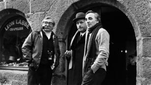 """Charles Aznavour discutant avec l'acteur Michel Serrault (au centre) et le réalisateur Claude Chabrol (à gauche) lors du tournage de """"Les Fantômes du chapelier"""" à Concarneau, le 20 janvier 1982."""