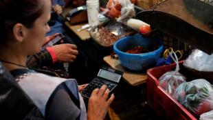 Una vendedora usa una calculadora para explicar los precios a un cliente en un puesto en un mercado municipal en Caracas, Venezuela el 21 de agosto de 2018.