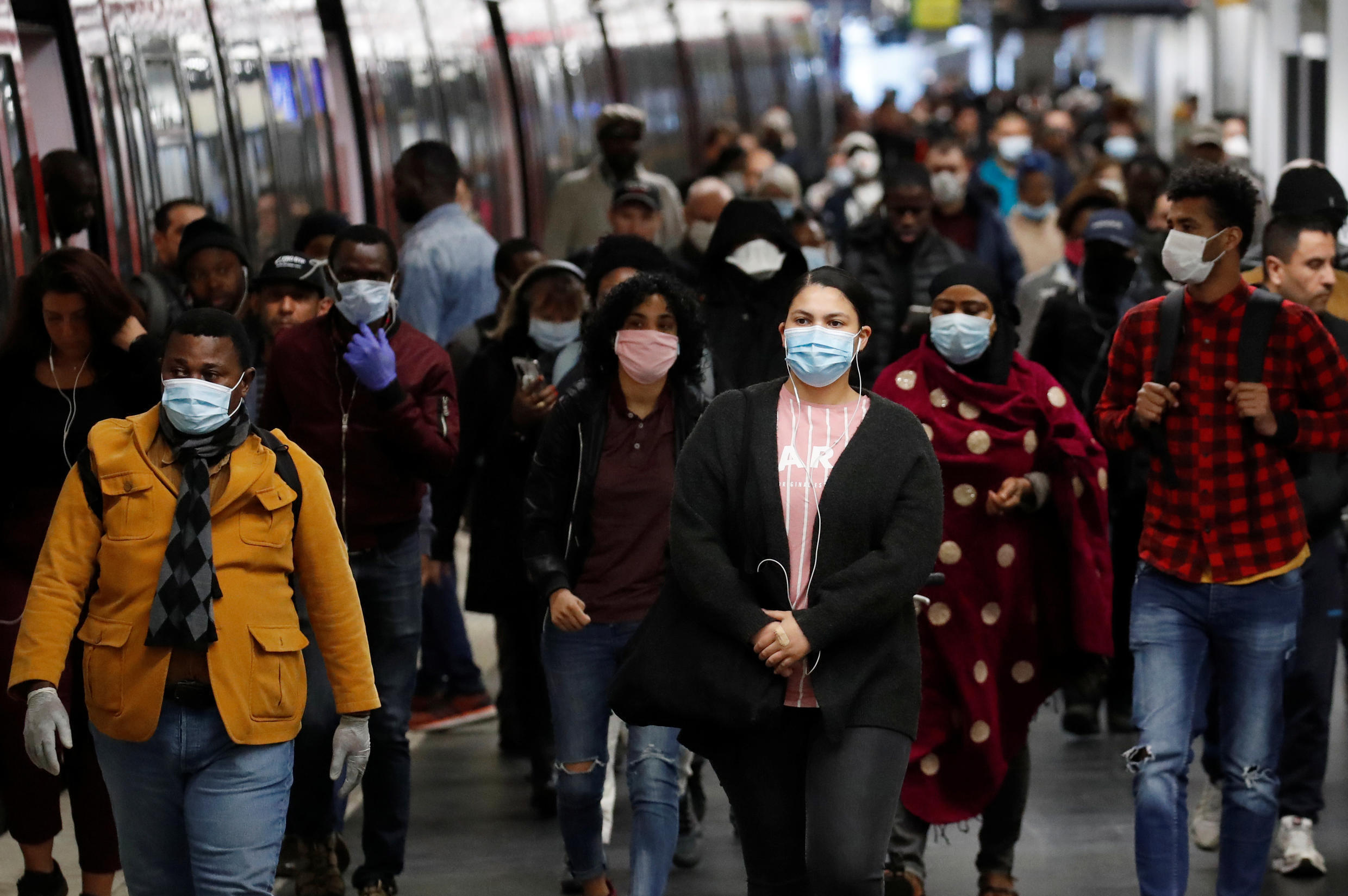 Commuters wearing protective face masks make their way along a suburban train platform as they arrive at the Gare du Nord RER station in Paris during a lockdown imposed to slow the spread of Covid-19 in France on April 27, 2020.