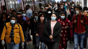 Commuters wearing protective face masks make their way along a suburban train platform as they arrive at the Gare du Nord RER station in Paris during a lockdown imposed to slow the rate of Covid-19 in France, April 27, 2020.