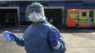 Un enfermera desinfecta unas ambulancias que trasladaron a pacientes de coronavirus el 24 de marzo de 2020 en el hospital de Brest, en Francia
