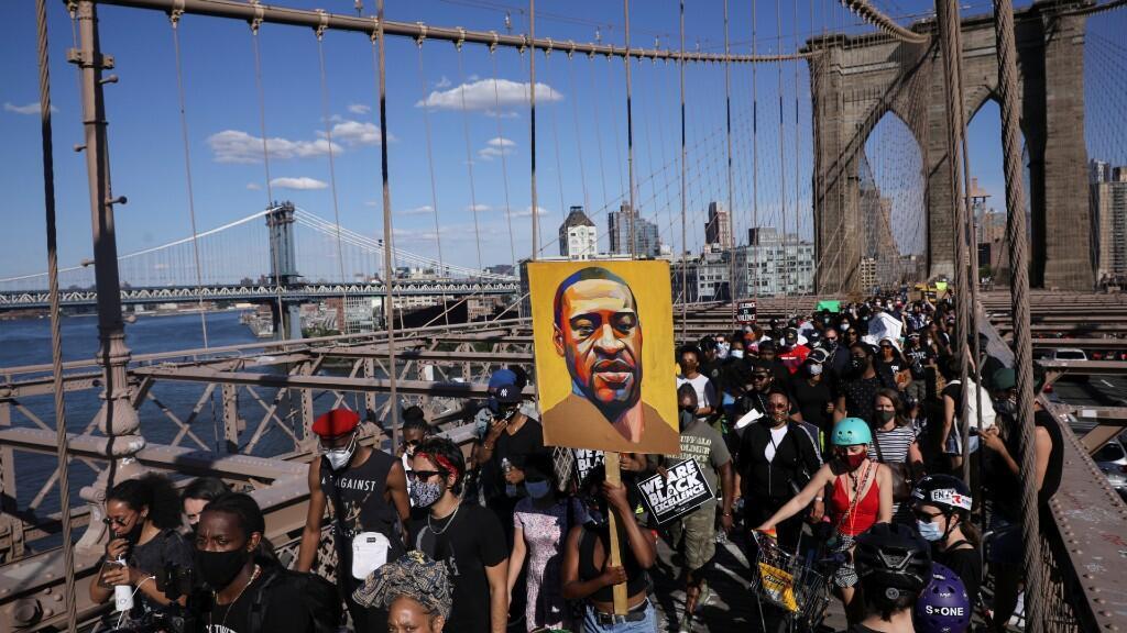 Los manifestantes sostienen carteles en el puente de Brooklyn durante una protesta contra la brutalidad policial y la desigualdad racial tras la muerte en custodia policial de George Floyd en Minneapolis. En Nueva York, Estados Unidos, 13 de junio de 2020.