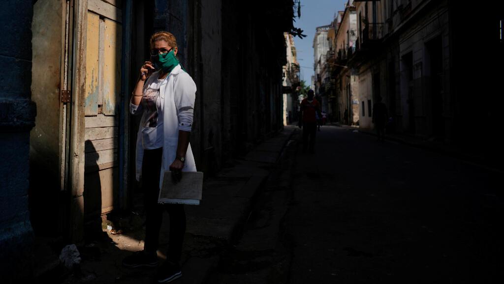 La profesional de la salud Mari García espera frente a la puerta de una casa en La Habana, Cuba, para examinar a una familia durante el Covid-19 el 30 de marzo de 2020.
