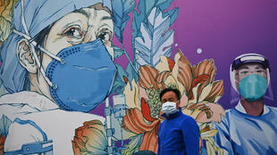 A man wearing a face mask walks past a mural at Leishenshan Hospital in Wuhan in April