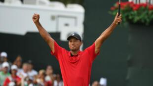 Tiger Woods eleva sus brazos en señal de triunfo tras ganar el torneo de golf Tour Championship en East Lake, Atlanta.
