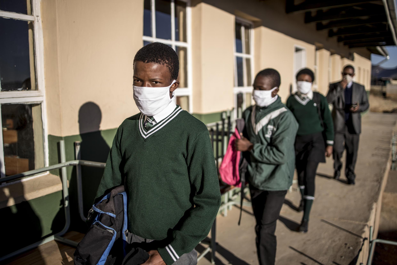 Estudiantes con mascarilla se disponen a entrar a clase en una escuela de secundaria de Sterkspruit, el 6 de julio de 2020 en el centro-este de Sudáfrica.