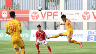 Phan Duc Thong (red shirt) of Pho Hien FC watches as Nguyen Vu Hoang Duong (right) of Thanh Hoa FC plays the ball during their Vietnamese National Football Cup qualifier match at the PVF stadium in Hung Yen in May after football resumed in Vietnam following a lockdown to halt the spread of coronavirus